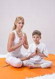 A beautiful  mother practices yoga with her son Royalty Free Stock Photo