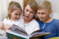 Beautiful mother is reading a book to her young children. Sister and brother is listening to a story. royalty free stock photo