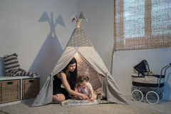 Beautiful mother reading to daughter in a teepee royalty free stock image