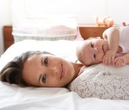 Beautiful mother rest in bed with baby daughter. Close up portrait of a beautiful mother rest in bed with baby daughter Stock Images