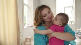 Beautiful mother rocking her baby girl to sleep stock footage