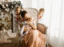 Beautiful mother sits with her little baby in the armchair next to the fireplace in the light cozy room and her two stock photos