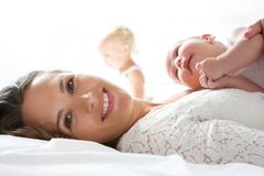 Beautiful mother smiling in bed with baby. Close up portrait of a beautiful mother smiling in bed with baby Royalty Free Stock Image