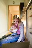 Beautiful mother with son in the arms, working on laptop. Beautiful young blond mother at home with her little baby son in the arms, sitting on the kitchen Stock Image