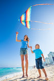 Beautiful mother and son holding arms with kite Royalty Free Stock Images
