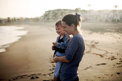 Beautiful mother and son playing on the beach Stock Image