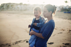 Beautiful mother and son playing on the beach Stock Photos