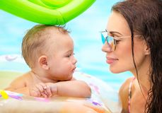 Beautiful mother with son in the pool. Closeup portrait of a beautiful mother with cute little baby in the pool, first lesson of swimming, enjoying summer Stock Photography