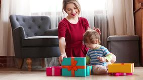 Beautiful mother with son wrapping a gift boxes stock video footage