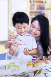 Beautiful mother teach son how to paint easter egg Stock Images