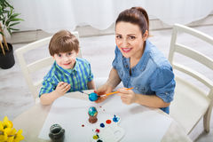 Beautiful mother teach son how to paint easter eggs Royalty Free Stock Images