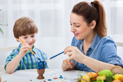 Beautiful mother teach son how to paint easter eggs Royalty Free Stock Image
