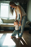 Beautiful mother teaches baby to walk Stock Photos