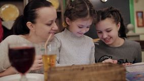 Beautiful mother with two daughters in cafe using phone and laughing. Time with family in a cafe. Mother and daughter in cafe using phone and laughing stock video