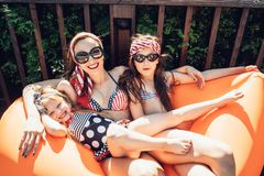 Beautiful mother with two daughters sitting on an orange lounge. Summer time vacations royalty free stock photos