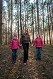 Beautiful mother walking with daughters at forest Royalty Free Stock Photo