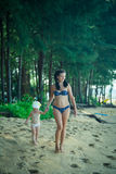 Beautiful mother walking with little daughter along the beach Stock Photography