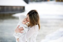 Beautiful mother in white dress and cute baby boy in knitted one. Sie, having taken their beautiful winter outdoor portrait on a sunny winter snowy day Royalty Free Stock Photography