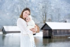 Beautiful mother in white dress and cute baby boy in knitted one. Sie, having taken their beautiful winter outdoor portrait on a sunny winter snowy day Stock Photos