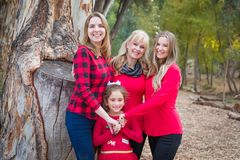 Pretty Mother With Daughters and Mixed Race Grandchild. Beautiful Mother With Young Adult Daughters and Mixed Race Granddaughter Portrait Outdoors stock photo