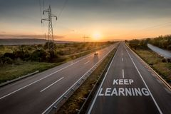 Beautiful Motorway with a Single Car at sunset with motivational message Keep Learning. Beautiful Countryside Motorway with a Single Car at sunset with royalty free stock photo