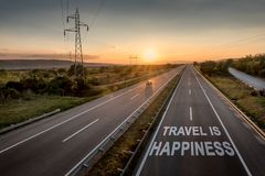 Beautiful Motorway with a Single Car at sunset with motivational message Travel Is Happiness. Beautiful Countryside Motorway with a Single Car at sunset with royalty free stock image