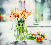 Beautiful mottled tulips bunch in glass vase at window with spring nature. Parrot tulips Stock Image