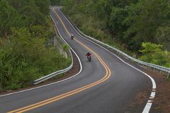 Beautiful mountain asphalt road with curve and double yellow lin. E, road runs along the edge of the forest in north thailand with two bikers riding big Royalty Free Stock Images