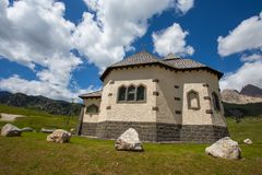 Beautiful mountain church under a sunny blue sky with clouds/Trentino/Dolomites/Italy. /Europe Stock Photo