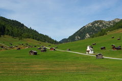 Beautiful mountain huts with small church in high Stock Photo