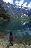 Beautiful Mountain Lake. A hiker pauses to enjoy the beautiful mountain and lake scenery at Lake Marian in the Fiordland National Park, South Island, New Zealand Stock Photography