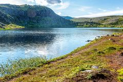 Beautiful mountain landscape with lake, green shore, blue sky stock image