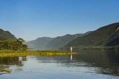 Beautiful mountain lake with fisherman Royalty Free Stock Image