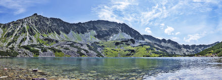 Beautiful mountain lake in tatry. Mountain panorama with lake, forest and blue sky. Poland, Zakopane - dolina pięciu stawów Royalty Free Stock Photography
