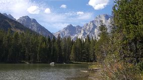 A beautiful mountain lake with the towering Tetons in the background. stock photo