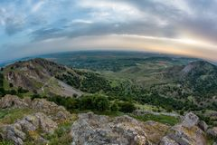 Beautiful mountain landscape with a cloudy sunset sky over the hills. Dobrogea, Romania Royalty Free Stock Photography