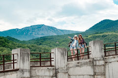 Beautiful mountain landscape, concrete bridge, two girls. Two girls in hats and glasses are traveling through a mountain valley through a concrete abandoned Stock Photo