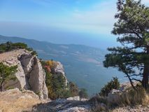 Beautiful mountain landscape from Crimean highest mountain Ai-Petri. The white rock massif in left and fragment of pine in right. Place for your text royalty free stock photo