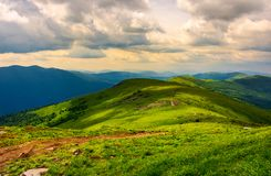Beautiful mountain landscape with grassy hills. Sky with fluffy clouds. foot path in to the distance Stock Images