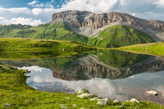 Beautiful mountain landscape. High rock and clouds reflected in Stock Photos