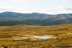 A beautiful mountain landscape with a lake in the distance. Autumn mountains in Norway. Stock Photos