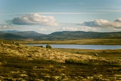 A beautiful mountain landscape with a lake in the distance. Autumn mountains in Norway. Royalty Free Stock Images