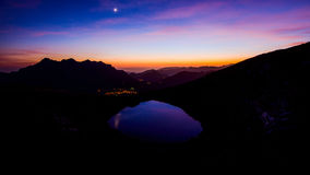 Beautiful mountain landscape with moon and little lake. Beautiful mountain landscape at sunset with moon and little lake Royalty Free Stock Photo