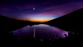 Beautiful mountain landscape with moon and little lake. Beautiful mountain landscape at sunset with moon and little lake Royalty Free Stock Images