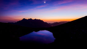Beautiful mountain landscape with moon and little lake. Beautiful mountain landscape at sunset with moon and little lake Stock Image