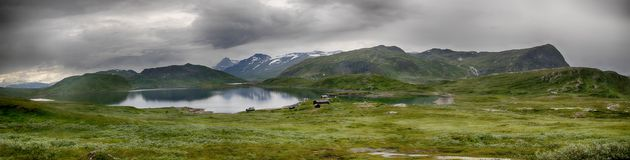 Beautiful mountain landscape panorama with lake and clouds. Panoramic view of Norway nature during summer vacation trip Stock Image