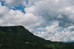 Beautiful mountain landscape, with mountain peaks covered with f. Orest and a cloudy sky stock photos
