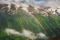 Beautiful mountain landscape with rainbow and clouds Stock Photo