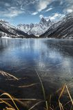 Beautiful mountain landscape in reflection of a frozen lake stock photo