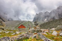 A beautiful mountain landscape. Tourist hut. Stone identification pyramid. Clouds. Grass and stones in the foreground. The Central Caucasus Royalty Free Stock Photography